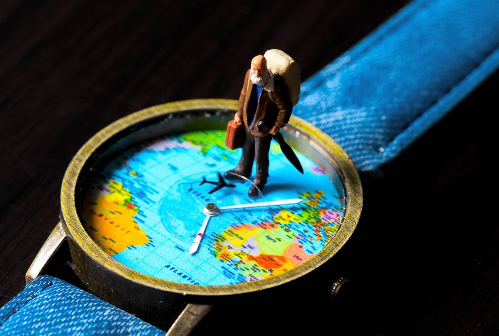 concept of an old man standing on a watch with a map of the worl on it